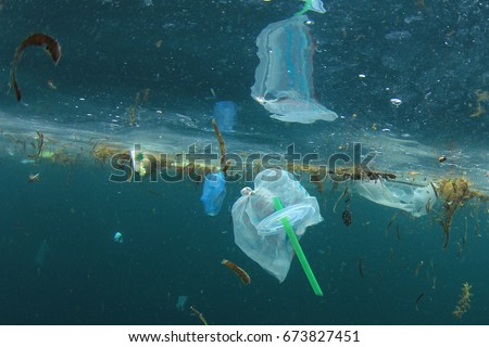 Plastic carrier bags and straws pollution in ocean Royalty-Free Stock Photo #673827451