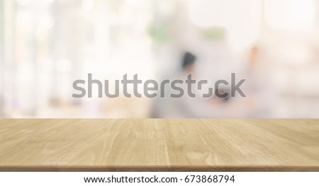 Wood table top and blurred restaurant kitchen interior background - can used for display or montage your products. #673868794
