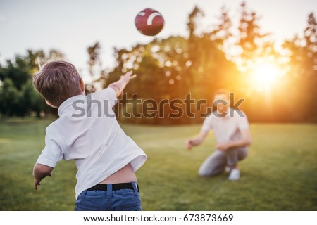 Handsome dad with his little cute sun are having fun and playing American football on green grassy lawn Royalty-Free Stock Photo #673873669