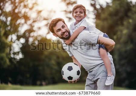 Handsome dad with his little cute sun are having fun and playing football on green grassy lawn #673879660