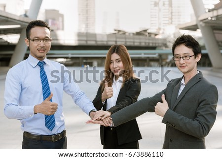 Group of young business man and woman united hands ant raised thumb represents pleasure together with spirit teamwork  on city background - success teamwork concepts or collaboration concepts. #673886110