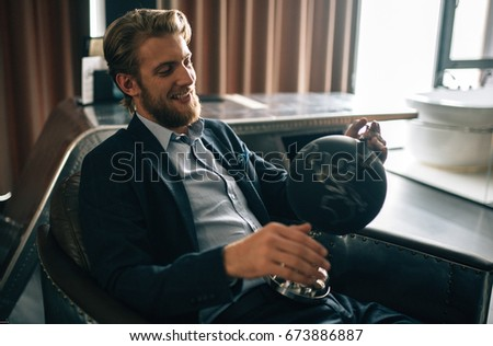 young stylish groom sits in the chair and keeps globe in his hands #673886887