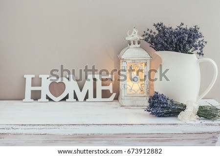 Shabby chic interior decor for farmhouse. Lavender in pitcher, lantern and wooden letters on a vintage shelf over pastel wall. Provence home decoration. #673912882