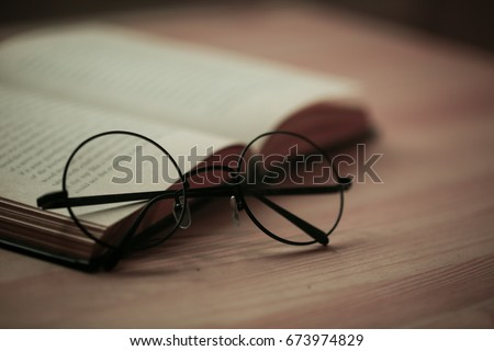 round glasses on a book #673974829