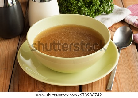 Bone broth made from beef, served in a green soup bowl #673986742
