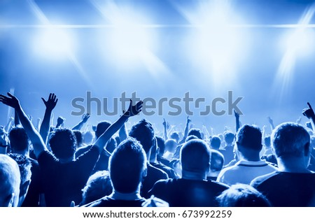 cheering crowd at rock concert in front of bright lights #673992259