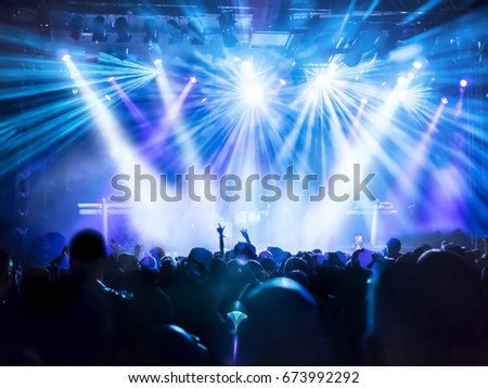 cheering crowd at rock concert in front of bright lights #673992292