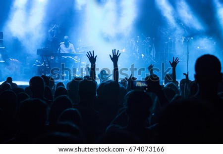 Photo of many people enjoying concert, crowd with raised up hands dancing in nightclub, audience applauding to musician band, night entertainment, music festival. #674073166