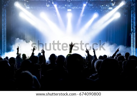 cheering crowd at rock concert in front of bright lights #674090800