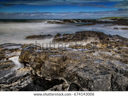 Long time exposure of waves around rocks at the Wild Coast at the Indian Ocean in South Africa during summertime #674143006