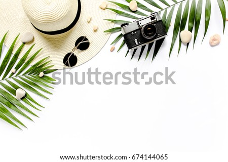 Traveler accessories, tropical palm leaf branches on white background with empty space for text. Travel vacation concept. Summer background. Road frame set. Flat lay, top view. Royalty-Free Stock Photo #674144065