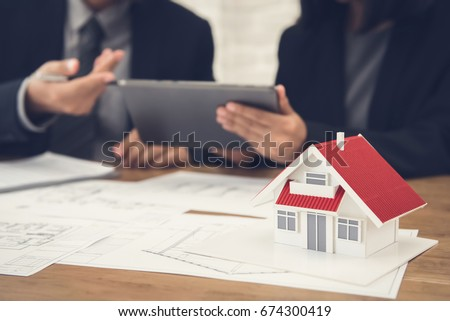 Real estate agent with client or architect team discussing project on tablet computer #674300419