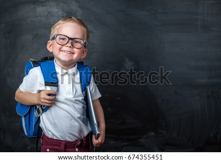 Happy cute clever boy in glasses with school bag and book in his hand.  Modern backpack. Child is ready to answer with a blackboard on a background. First time to school. Back to school.  #674355451