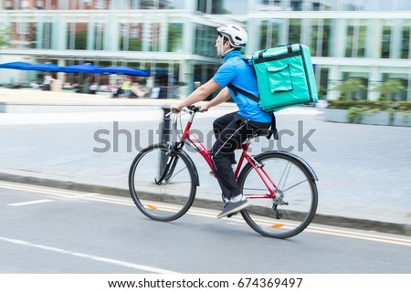 Courier On Bicycle Delivering Food In City #674369497