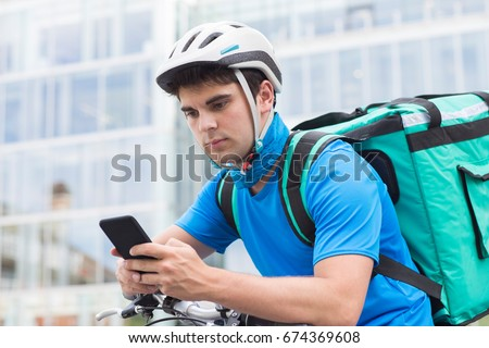 Courier On Bicycle Delivering Food In City Using Mobile Phone #674369608