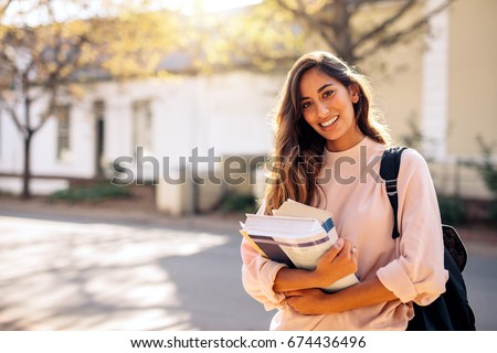 Beautiful young woman with backpack and books outdoors. College student carrying lots of books in college campus. #674436496