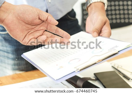 Close-up of businessman explaining a financial plan to colleagues at meeting #674460745