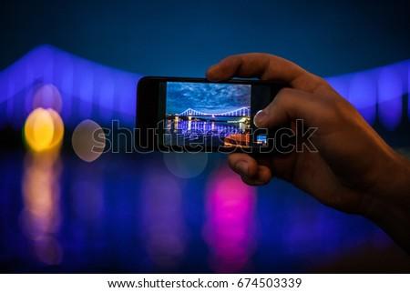 Man taking photo of luminous bridge on mobile phone at night. Smart phone travel photography