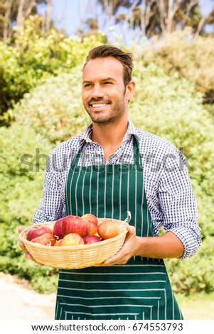 Smiling man with apple basket standing against trees on sunny day #674553793