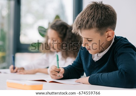 Concentrated schoolboy sitting at desk and writing in exercise book with classmate sitting behind #674559766