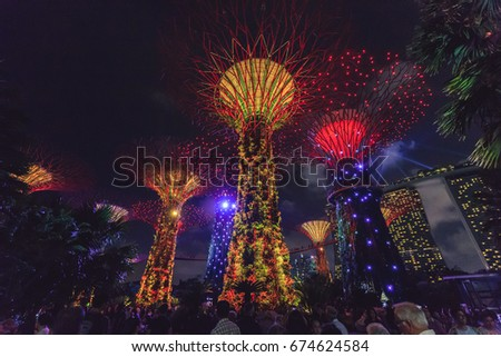 SINGAPORE - FEB 18, 2017: Night view of the Supertree Grove in the Garden by the Bay with Marina Bay Sands background in Singapore. #674624584