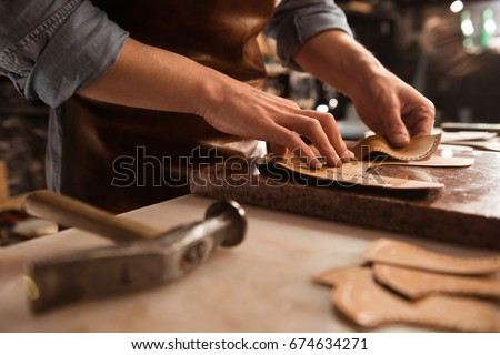Close up of a shoemaker working with leather textile and hammer at a workshop Royalty-Free Stock Photo #674634271