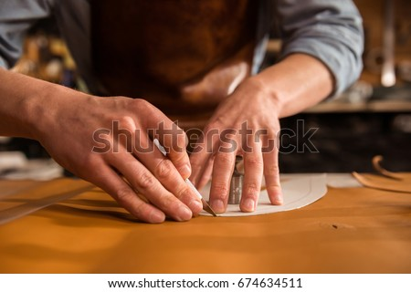 Close up of a shoemaker cutting leather in a workshop #674634511