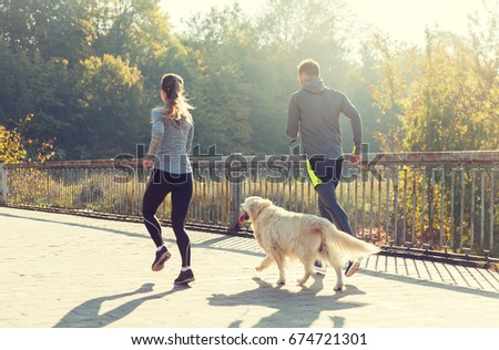 fitness, sport, people and jogging concept - close up of couple with dog running outdoors #674721301