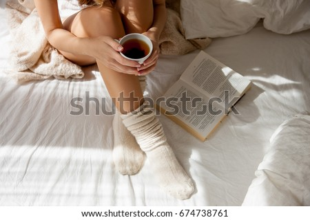 Beautiful Legs close-up in Bed. Woman is Drinking Tea and Reading a Book. Girl Sitting on a Bed in Woolen Socks. Beautiful Woman no Face. Legs. Attractive Model Wears  Woolen white Socks      #674738761