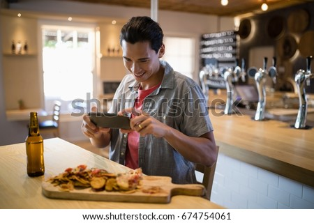 Smiling man taking a picture of food on his mobile phone in restaurant