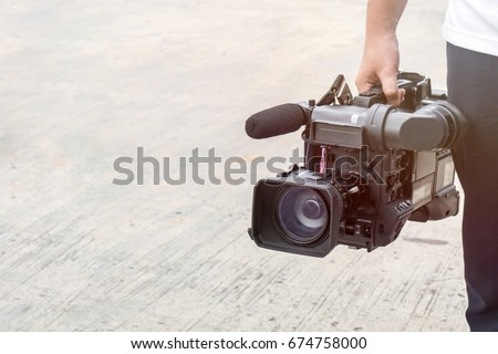 Photographer covering an event at outdoor with a video camera., with copy space for text. vintage style #674758000