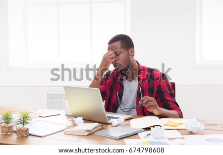 Sleepy black businessman in office, work with laptop, overworking and having headache #674798608