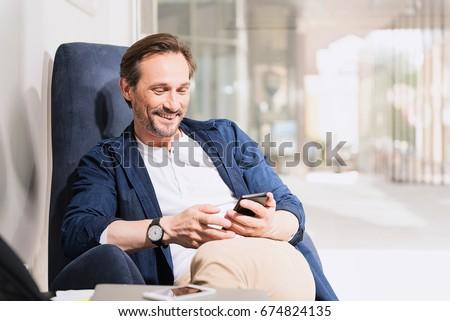 Happy senior man using mobile phone #674824135