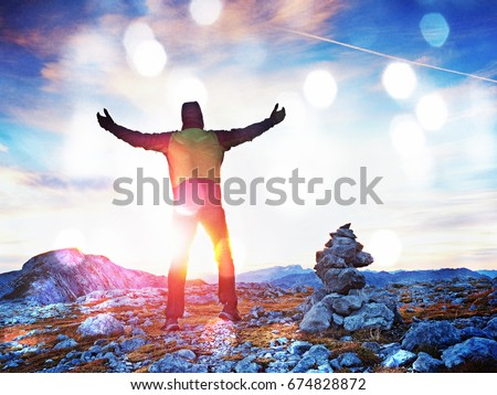 Film grain effect. Film scratch. Happy hiker with raised arms in the wind.  Tourist guide at stocked stones on Alps peak. Strong hiker enjoy sunset in   Alpine mountain.