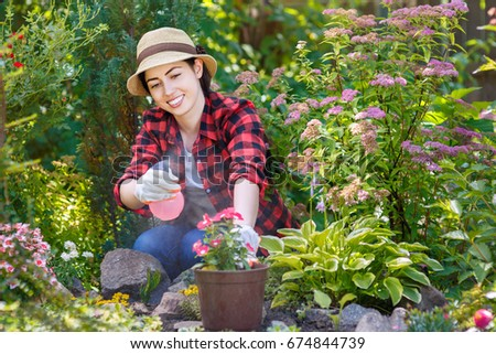 portrait of happy young woman gardener spraying water on plants. Hobby concept #674844739