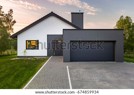 Modern house with garage and green lawn, exterior view Royalty-Free Stock Photo #674859934