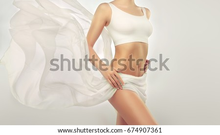 Perfect slim toned young body of the girl . An example of sports , fitness or plastic surgery and aesthetic cosmetology. Healthy Breast . Royalty-Free Stock Photo #674907361