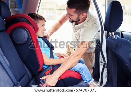Side view of small handsome son in car seat being put in back of car by father #674907373