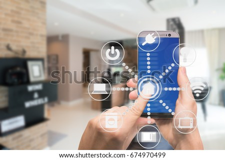 Smart home automation app on mobile with home interior in background. Internet of things concept at home. Smart technology 4.0 #674970499