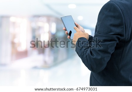 isolated business man hold the smartphone on shopping mall background #674973031