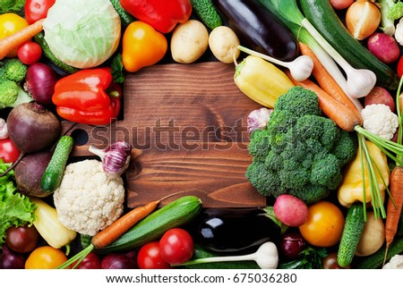 Autumn harvest farm vegetables, root crops and wooden cutting board top view with copy space for text. Healthy and organic food background. #675036280