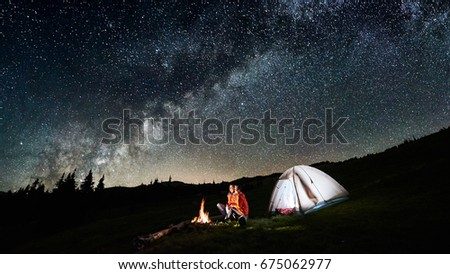 Night camping. Couple tourists sitting at a campfire near illuminated tent under incredible night sky full of stars and milky way. Long exposure. Picture aspect ratio 16:9