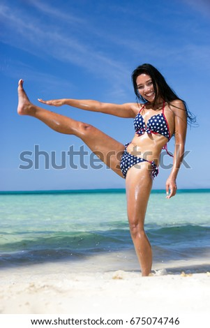 A happy cheerful girl in the bikini kicking out her leg at the beach. Active holidays on the tropical island. Beautiful asian woman jump in the transparent sea. #675074746