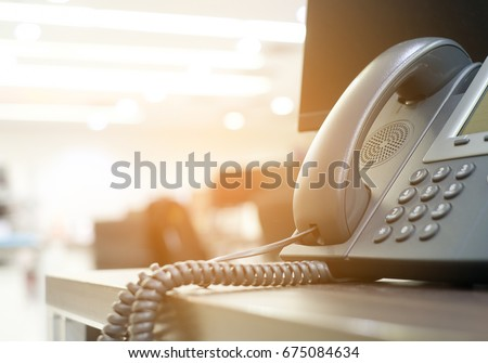 close up soft focus on telephone devices at office desk with light effect,communication technology concept Royalty-Free Stock Photo #675084634