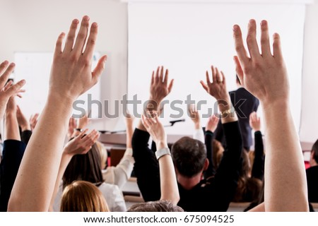 Raised hands and arms of large group of people in class room, audience voting in professional education surrounding, selective focus with anonymous people. Royalty-Free Stock Photo #675094525