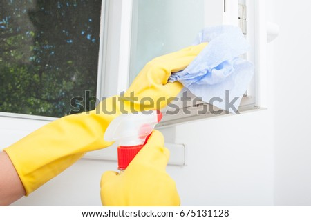 Female hand holding rag and wiping the bathroom window in closeup view #675131128
