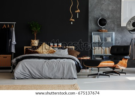 Eco style grey and black bedroom with comfortable bed and armchair #675137674