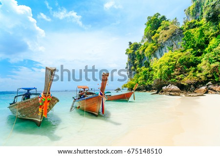 Longtale boat on the white beach at Phuket, Thailand. Phuket is a popular destination famous for its beaches. #675148510