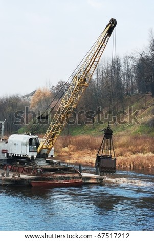 The dredge on the barge digs the channel in the river #67517212