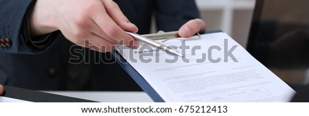 Male hand holding silver pen ready to make note in opened notebook sheet. Businessman in suit at workspace make thoughts records at personal organizer #675212413